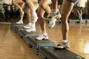 Low section view of a group of people exercising in a step aerobics class