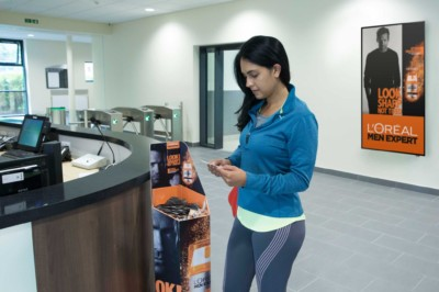Woman in exercise clothes next to product sampling in the gym