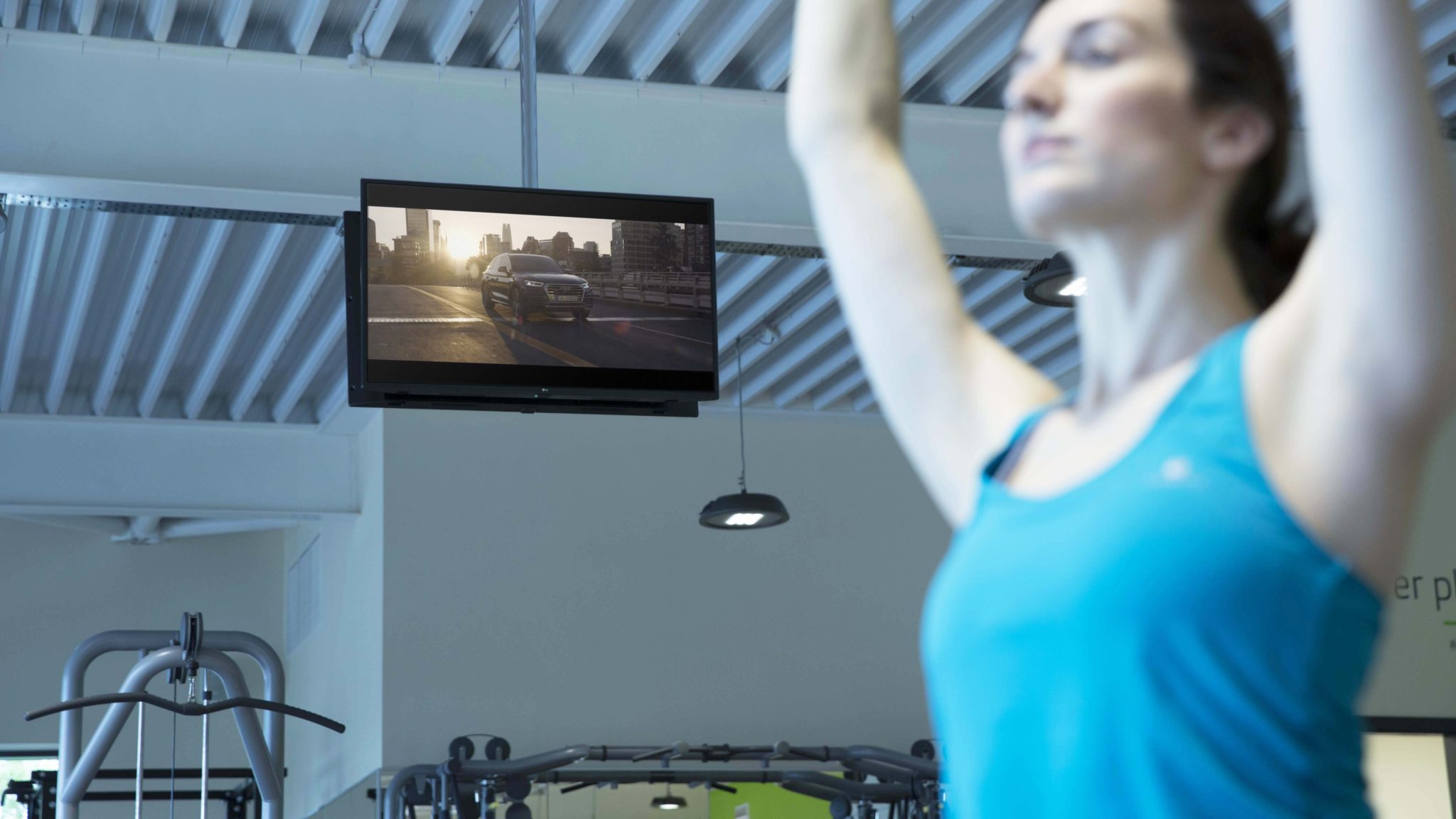 Woman in a blue tank top doing yoga in a gym while watching advertising on gym tv