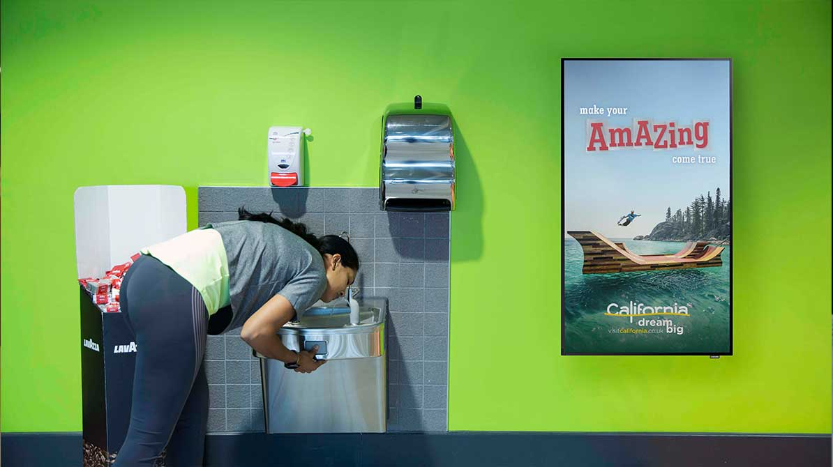 Woman at drinking fountain next to vertical digital screens showing gym tv advertising