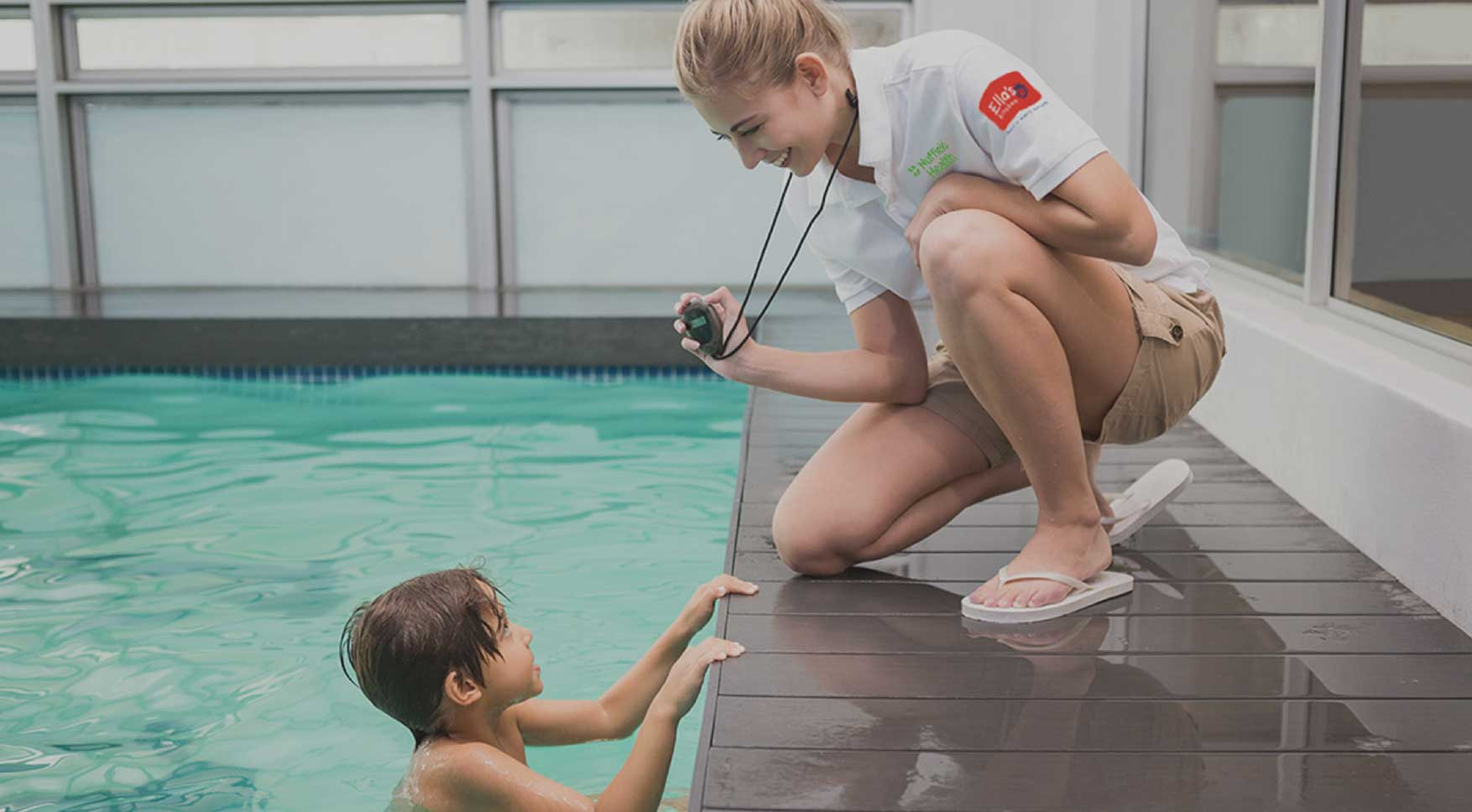 Woman in gym pool teaching a child swimming lessons